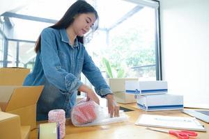 adolescentes estão embalando produtos com plástico à prova de choque para entregar aos clientes. foto