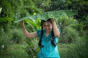 retrato de uma jovem asiática com cabelo preto segurando uma folha de bananeira na chuva no fundo do jardim verde foto