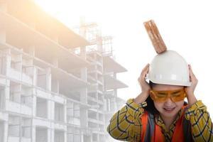 o tijolo do bloco de pau caiu na cabeça da jovem engenheira asiática sobre o trabalhador do capacete em fundo branco, conceito de segurança de construção de área primeiro foto