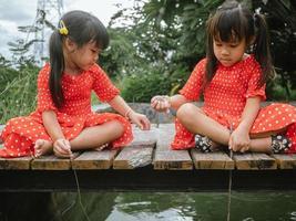 duas garotinhas no papel de vestido vermelho pescando sentado em uma ponte de madeira à beira da lagoa. felicidade infantil. foto