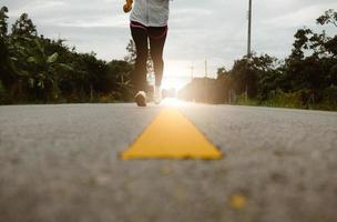 corredores femininos correndo na trilha de estrada no treinamento matinal para a maratona e fitness. conceito de estilo de vida saudável. atleta correndo exercício ao ar livre. pernas de close-up. foto