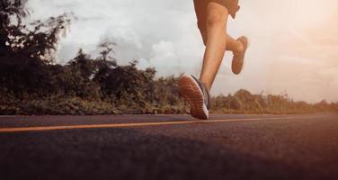 corredor de adolescentes correndo na rua para se exercitar. perto das pernas. conceito de estilo de vida saudável. foto