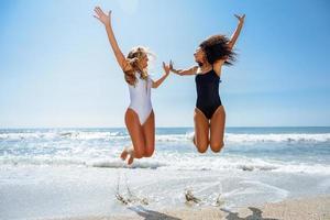 duas garotas engraçadas em maiô pulando em uma praia tropical foto