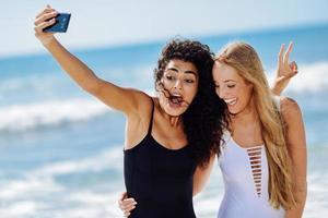 duas mulheres tirando foto de selfie com smartphone na praia