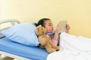 jovem asiática está deitada na cama do hospital e assistindo desenhos animados no tablet. conceito de saúde e médico foto