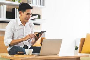jovem bonito asiático usando o computador para trabalhar em casa. conceito de negócios e tecnologia foto