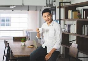 homem asiático sentado no café, bebendo café e café da manhã, woking a distância. conceito de negócios e tecnologia foto