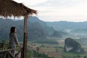 jovem mulher asiática sentindo relaxar e olhando para a paisagem do vale e das montanhas na manhã. conceito de viagens e férias foto