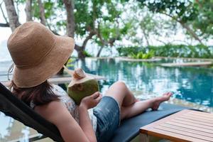 jovem com chapéu de palha e roupa casual sentada no banco perto da piscina e bebendo suco de coco nas férias de verão foto