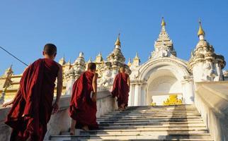 grupo de monge novato asiático descendo as escadas do mosteiro foto