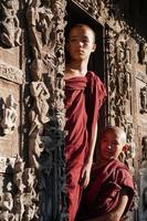 retrato de um grupo de monge novato asiático em pé na porta do templo foto