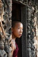 retrato sincero de um jovem monge noviço parado na porta do monastério foto