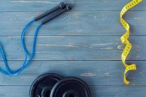 halteres com notebook, escalas, pular corda e garrafa de água no fundo de madeira. foto