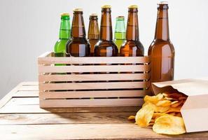 garrafas de cerveja e batatas fritas em uma mesa de madeira. vista do topo. foco seletivo. brincar. copie space.template. em branco. foto