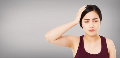 forte dor de cabeça de mulher coreana, sofrendo menina asiática isolada em fundo cinza foto