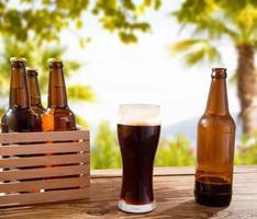 copo de cerveja escura na mesa de madeira com garrafas, fundo borrado de praia e palmas, conceito de comida e bebida, espaço de cópia, foco seletivo foto