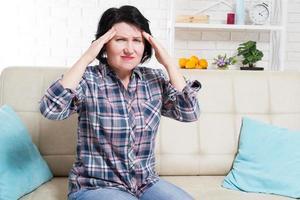 Mulher de meia-idade sofrendo de dor de cabeça e estresse, segurando as têmporas com as mãos e os olhos abertos de dor foto