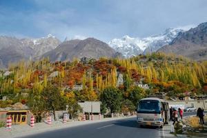 Hunza Valley, Paquistão, 2017 - turismo em Gilgit Baltistan na temporada de outono. árvores da floresta de folhagem colorida contra os picos das montanhas cobertas de neve na faixa de karakoram. foto