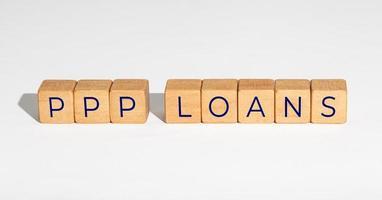 conceito de programa de proteção de cheque de pagamento de empréstimo ppp. blocos de madeira com texto em fundo branco. copie o espaço foto