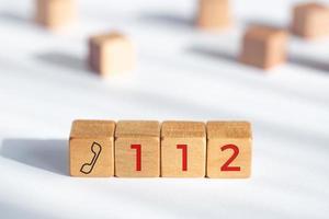 Conceito de emergência 112. dados de madeira com ícone de telefone e texto 112 foto