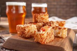 dados de tapioca com geleia de pimenta e copos de cerveja em uma tábua de madeira - close up. foto