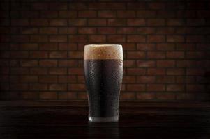 isolado copo suado de cerveja escura refrescante com fundo de parede de tijolos. foto