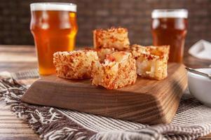 tapioca em cubos com geleia de pimenta e copos de cerveja em uma tábua de madeira foto