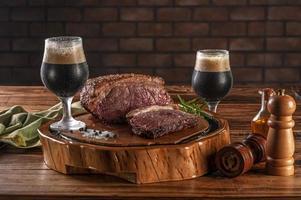 bife de alcatra grelhado na tábua de madeira com dois copos de tulipa suado de cerveja escura. foto