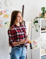 bela mulher artista com camisa xadrez pintando um quadro em casa foto