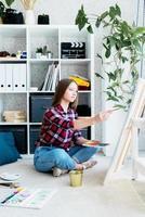 bela mulher artista pintando um quadro em casa foto