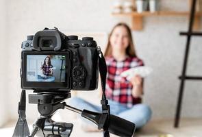 mulher fazendo um vídeo para seu blog sobre arte usando uma câmera digital montada em um tripé foto