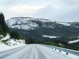 dirigindo pela estrada de neve branca e paisagem na Noruega. foto