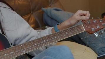 mão com o celular de um jovem homem do Oriente Médio segurando na frente da guitarra de uma jovem mulher de raça mista, girando o afinador de guitarra foto