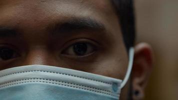 close-up extremo de homem negro com máscara facial, olhos olhando para a câmera foto