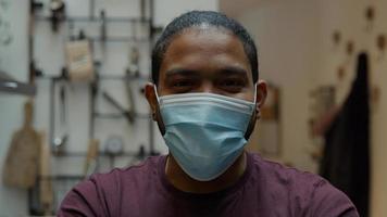 close-up do homem negro, olha para a lente da câmera, sorrindo, coloca máscara facial com as duas mãos, ajustando a máscara, olhos sorridentes foto