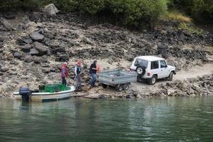 lugo, galicia, espanha, 2021. homens carregando uvas para terra após transportá-las de barco rio abaixo do vinhedo foto