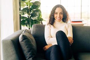 mulher latina sorrindo e sentada no sofá foto