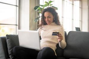 mulher latina usando laptop e segurando um cartão de crédito para fazer compras no sofá foto