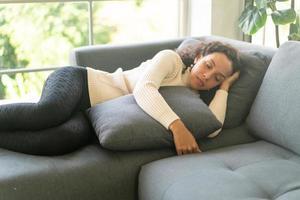 mulher latina dormindo no sofá foto