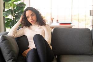 mulher latina sentada no sofá com um sentimento de solidão foto