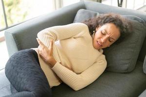 mulher latina deitada no sofá com dor de estômago foto