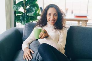 mulher latina tomando café no sofá foto
