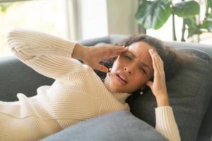 mulher latina deitada no sofá com dor de cabeça foto