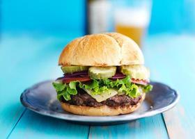 cheeseburger com cerveja no fundo foto