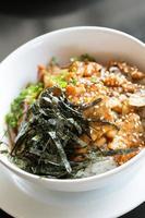carne de porco frita e arroz com algas por cima foto