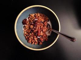 granola de abóbora caseiro com leite e colher em fundo escuro foto