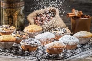 açúcar em pó caindo sobre bolos de baunilha foto