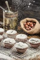 açúcar de confeiteiro caindo sobre bolos de chocolate frescos foto