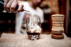 barman derramando licor alcoólico em copo pequeno no balcão foto