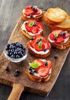 pão torrado com frutas e creme de queijo foto